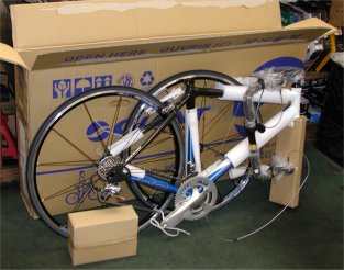 This is how a bike arrives at a bike shop.  Try and replicate this when packing your own road bike. Notice the box as protection against the rear derailleur being squashed!