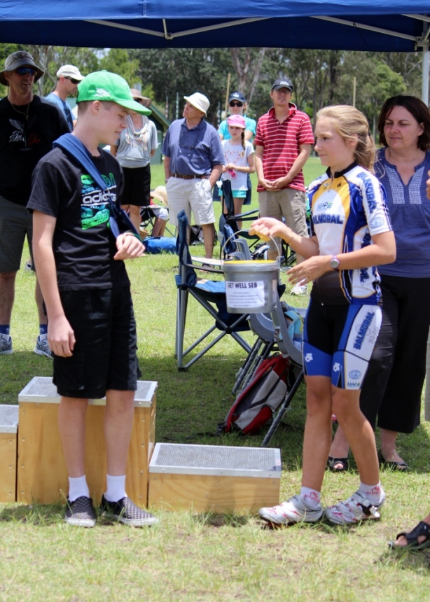 Seb being given the bucket of money raised for him at the NJTS.