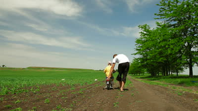 stock-footage-father-helping-child-learn-to-ride-a-bike